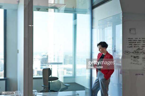 silhuet of businesswoman tjecking phone in office with glass walls - red jacket stock pictures, royalty-free photos & images