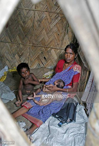 Indian woman Mina Devi Singh holds her infant twin daughters Laxmi and Saraswati as her son Etowari sits close by in a shanty in a slum area in the...