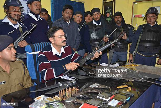 Siliguri Police Commisioner Jag Mohan handles a seized weapon during a news conference at the NJP outpost in Siliguri on January 30 2014 Nine people...