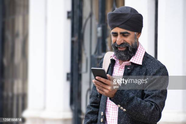 silk businessman with turban using smart phone - punjab - india stock pictures, royalty-free photos & images