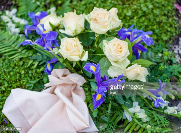 Silk flowers on a gravestone, Flowers on a cemetery