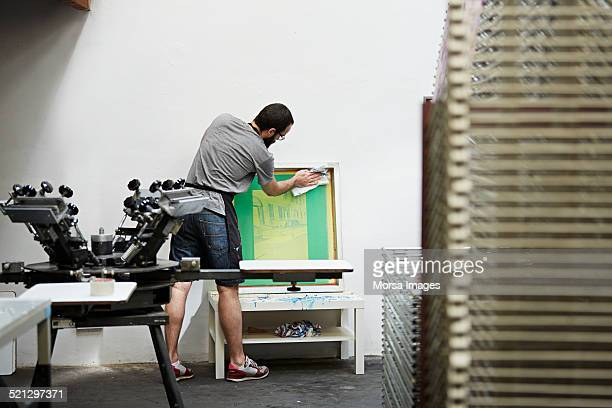Silk screen worker cleaning screen