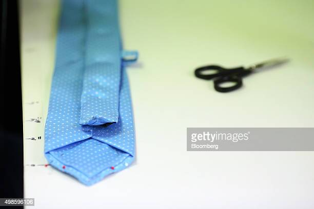 A silk tie lies on the cutting table at the Emma Willis luxury designer menswear factory in Gloucester UK on Tuesday Nov 24 2015 Digital luxury goods...