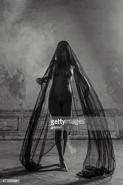Silk wrapped naked woman walking in old castle room