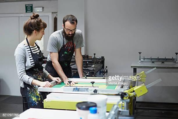 Silkscreen workers checking silk on printing table