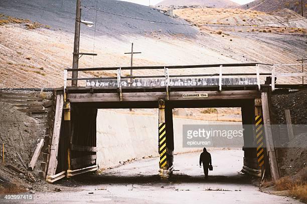 Silloutte der arbeitenden Mann zu Fuß unter industrial railroad bridge