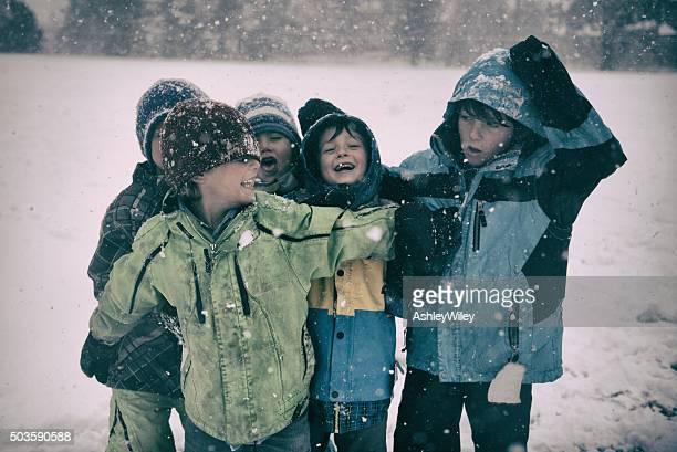 Lustige Kinder spielen in einem Schneesturm in Jacken und -Hüte