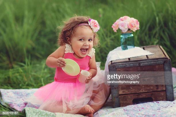 Silly little girl with a teacup and saucer