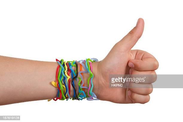 de forma más desenfadado banda de hule bracelets, mano con thumbs up - pulsera fotografías e imágenes de stock