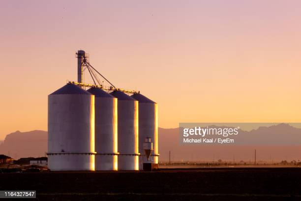 silo on lands against sky during sunset - silo stock photos and pictures