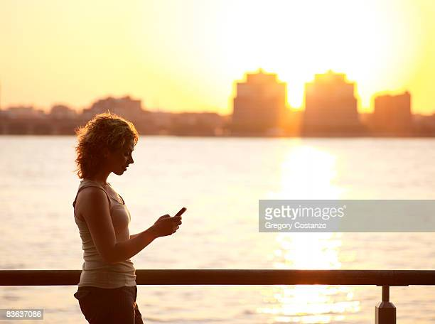 Silohuette of a woman at sunset with cell phone