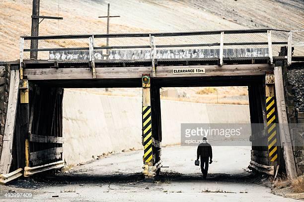 Silouette Blue Collar worker zu Fuß unter railroad bridge
