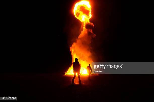 silouette of firemen infront of big fire with fireball - explosives stock photos and pictures