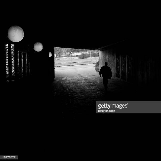 CONTENT] silouhette of a man walking in a tunnel