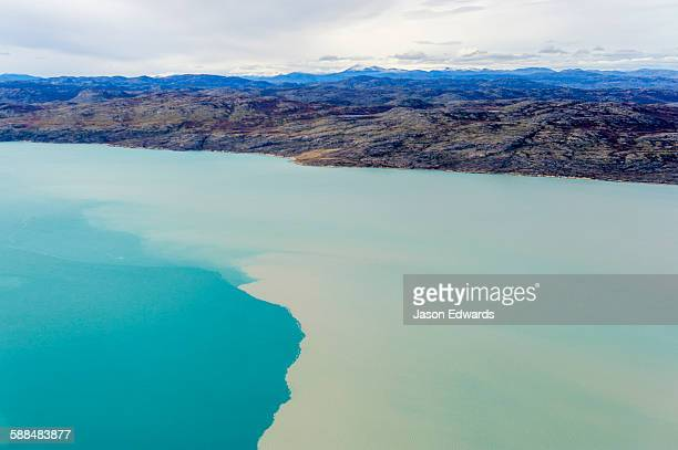 Silt from a river outwash plain stains the blue water of a fjord.