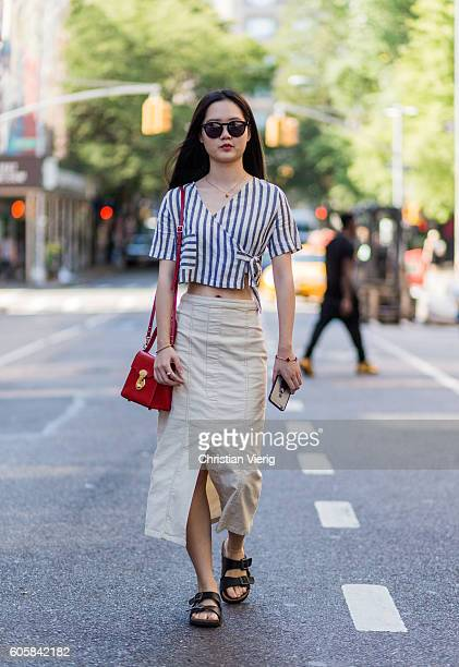 Silu Xu wearing a beige skirt Birkenstock sandals and a white blue striped top outside Hugo Boss on September 14 2016 in New York City