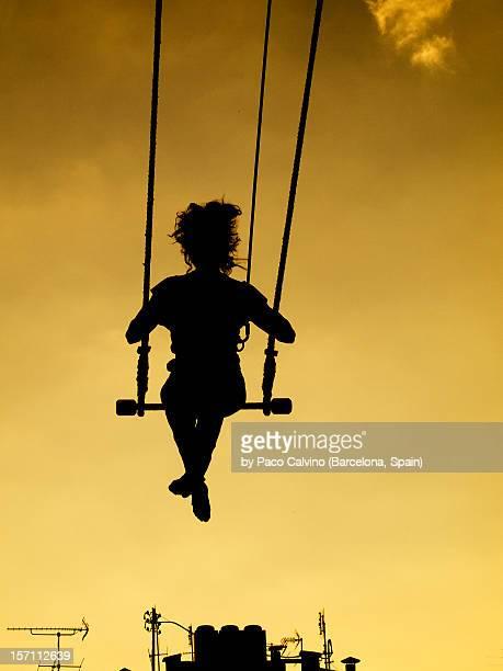 silueta de mujer en trapecio con fondo calido - trapeze artist stock photos and pictures