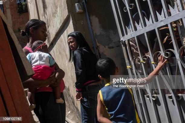 Silvana Aguirre a neighborhood activist talks to a neighbor in her neighborhood of El Carpintero in Petare Venezuela on February 10 2019 She has...