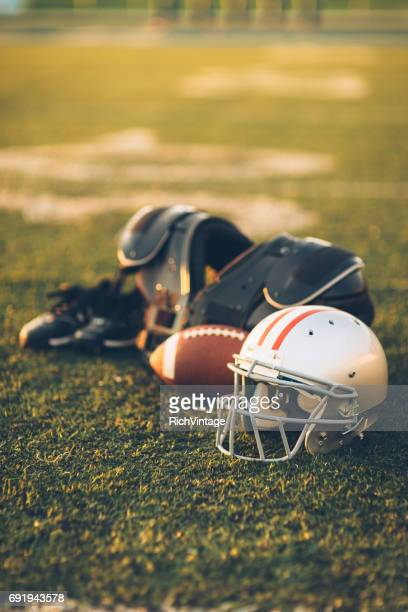 silver american football helmet on field - ohio state helmet stock photos and pictures