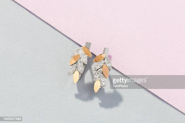 silver and gold earrings in leaves shape decorated with diamonds on pink and gray background - ohrring stock-fotos und bilder