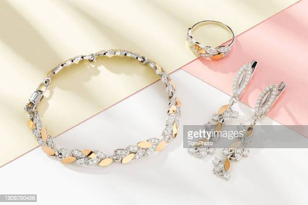 silver and gold set of jewelry in leaves shape decorated with diamonds. bracelet, earrings and ring - white gold stock pictures, royalty-free photos & images