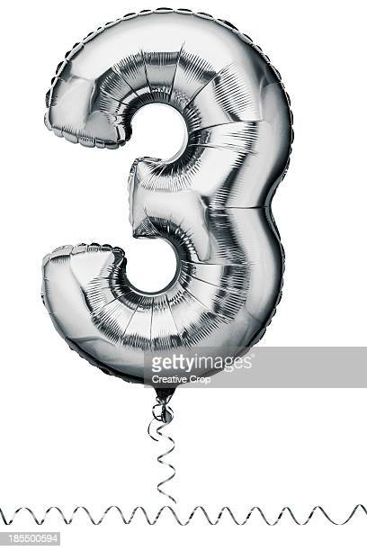 Silver balloon in the shape of a number three
