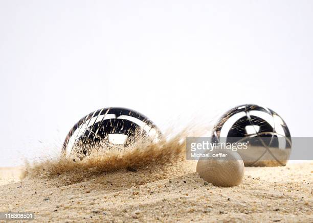 A silver boule landing near the white ball on the beach