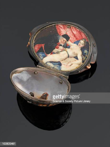 Silver bound cowrie shell Silver bound cowrie shell hinged opening out to reveal a small painting of a male unlocking the chastity belt of a female...