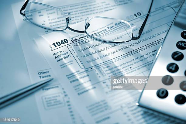 silver calculator glasses and pen on US tax return form