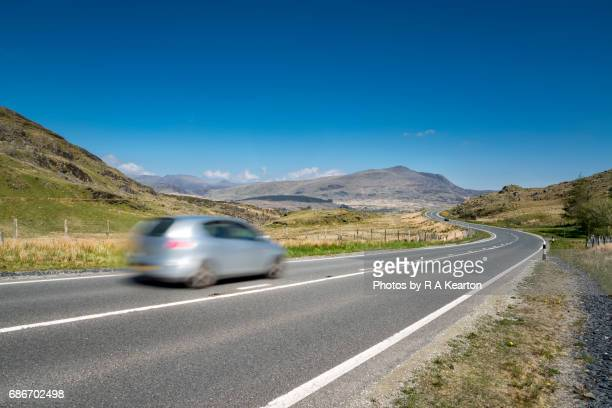 Silver car speeding along a road in Snowdonia, North Wales, UK