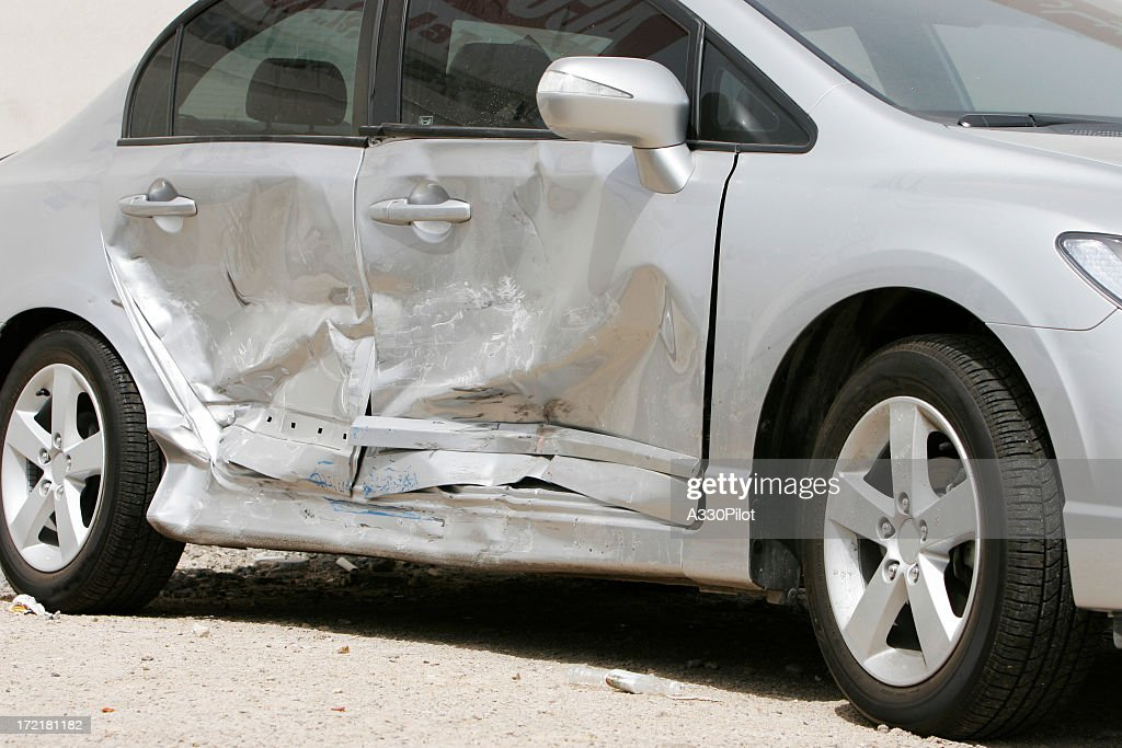 Silver car with a large dent in the side, ruining two doors : Stock Photo
