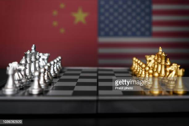 silver chess against gold chess with usa and china flag. design creative illustration for usa and china trade war. - us china trade war stock pictures, royalty-free photos & images
