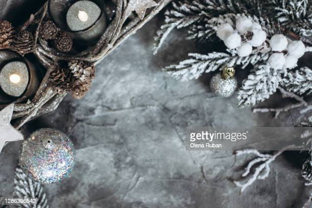 silver christmas toys, snow-covered fir-tree branches and a candlestick - christmas decore candle stock pictures, royalty-free photos & images