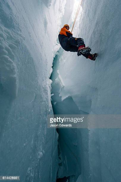 A cameraman descending the sheer icy walls of a crevasse on the slopes of Mount Erebus in Antarctica.