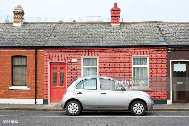 Silver compact car parked outside brick home