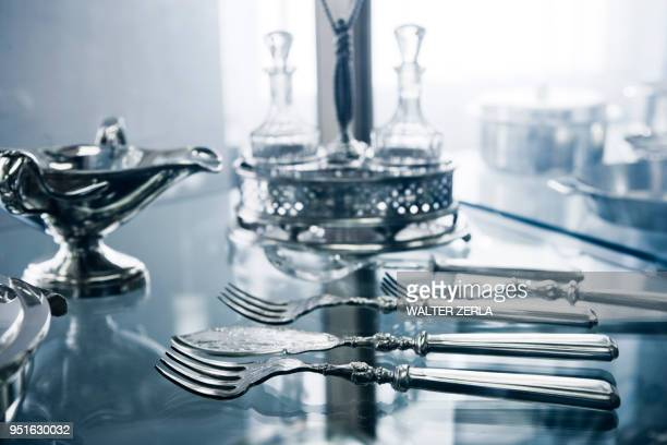 silver cutlery, gravy boat and cruet in display cabinet - cruet stock photos and pictures