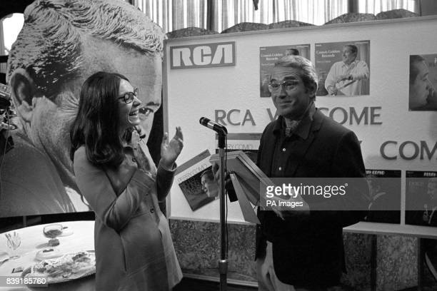 A silver disc for American singer Perry Como presented to him by Greek singer Nana Mouskouri He received the award for his recording It's Impossible