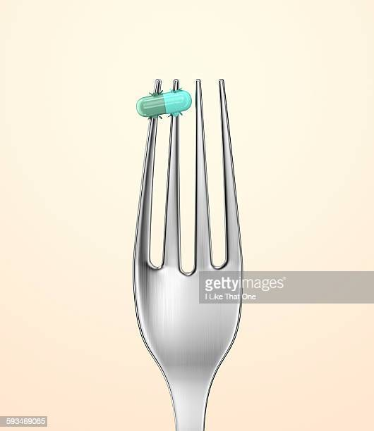 Silver fork with a pill spiked on a prong