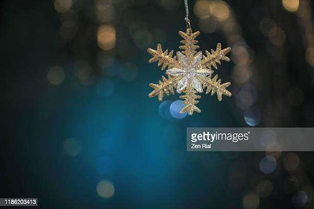 silver gold colored star-shaped christmas ornament hanging against defocused teal background - christmas still life stock pictures, royalty-free photos & images