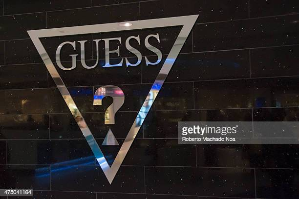Silver Guess clothing store signage on black tiles with the word Guess and a question mark inside an inverted triangle
