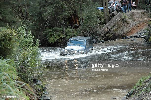silver jeep tj wrangler mid stream in creek crossing - jeep wrangler stock photos and pictures