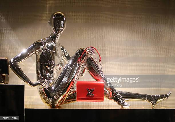 A silver mannequin holds a luxury red handbag in the window display of an LVMH Moet Hennessy Louis Vuitton SE fashion boutique at the GUM department...