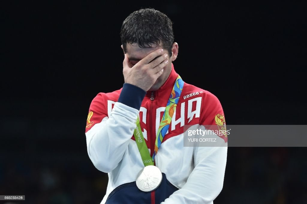 TOPSHOT - Silver mealist Russia's Misha Aloian react during the medal presentation ceremony following the Men's Fly (52kg) Final Bout at the Rio 2016 Olympic Games at the Riocentro - Pavilion 6 in Rio de Janeiro on August 21, 2016. /