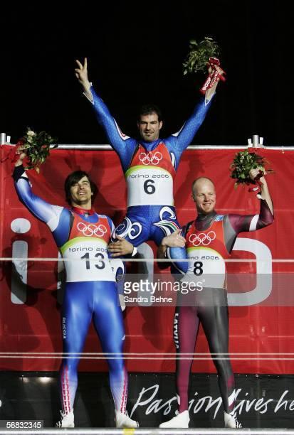 Silver Medal winner Albert Demtschenko of Russia and Bronze Medal winner Martins Rubenis of Latvia hold up Gold Medal winner Armin Zoeggeler of Italy...