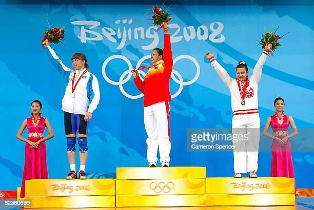 Silver medal winner Alla Vazhenina of Kazakhstan gold medal winner Cao Lei of China and bronze medal winner Nadezda Evstyukhina of Russia wave to the...