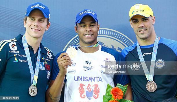 Silver medal winner Cesar Cielo gold medal winner Matheus Santana and bronze winner Joa de Lucca celebrate on the podium after swimming in the Men's...