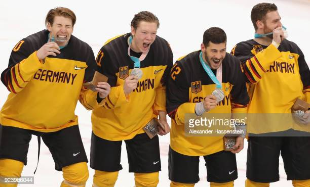 Silver medal winners Bjoern Krupp Jonas Mueller Yazin Ehliz and Gerrit Fauser react during the medal ceremony after being defeated by Olympic...