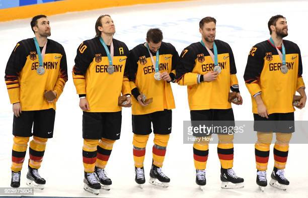 Silver medal winners Daryl Boyle Christian Ehrhoff Brooks Macek Marcus Kink and Matthias Plachta of Germany look on during the medal ceremony after...