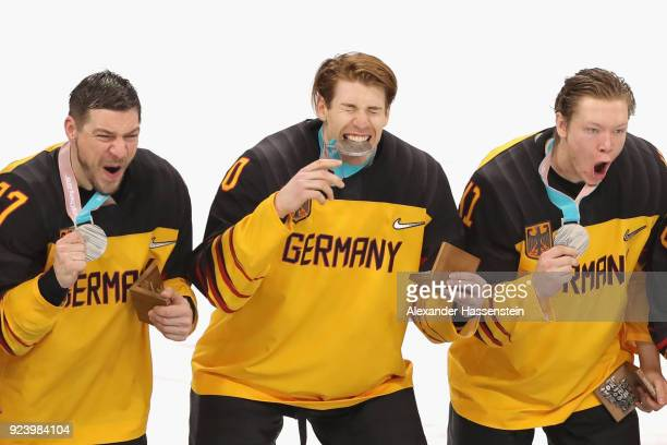 Silver medal winners Patrick Reimer Bjoern Krupp and Jonas Mueller react during the medal ceremony after being defeated by Olympic Athletes from...