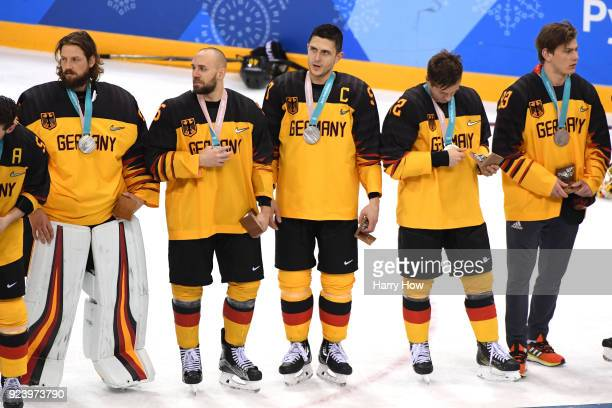 Silver medal winners Timo Pielmeier Felix Schutz Marcel Goc Dominik Kahun and Leonhard Pfoderl of Germany look on during the medal ceremony after...